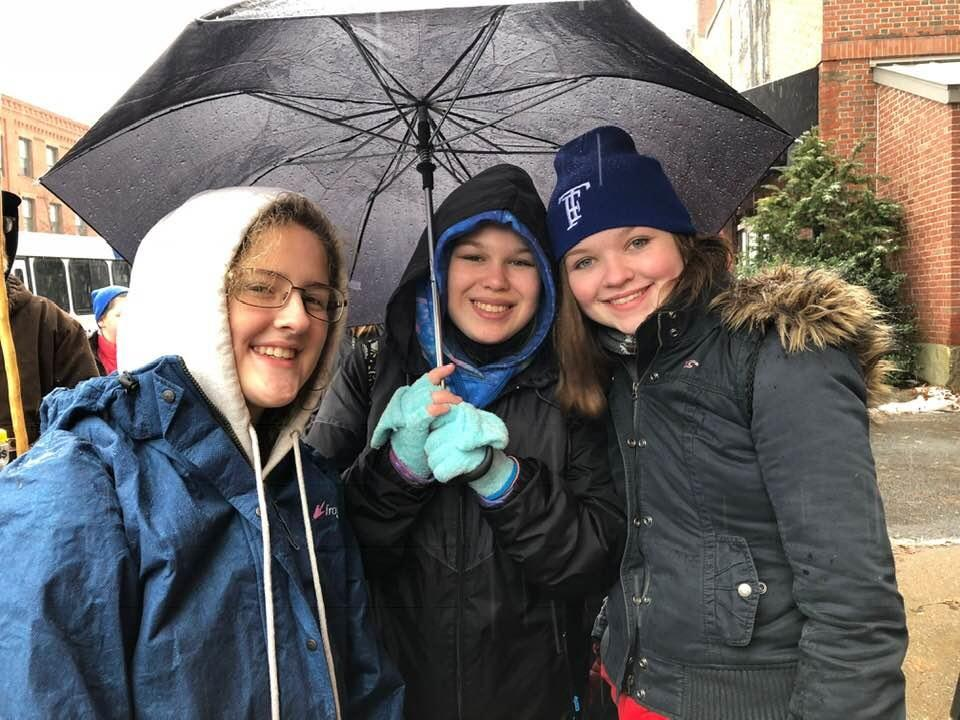 three students outside beneath an umbrella