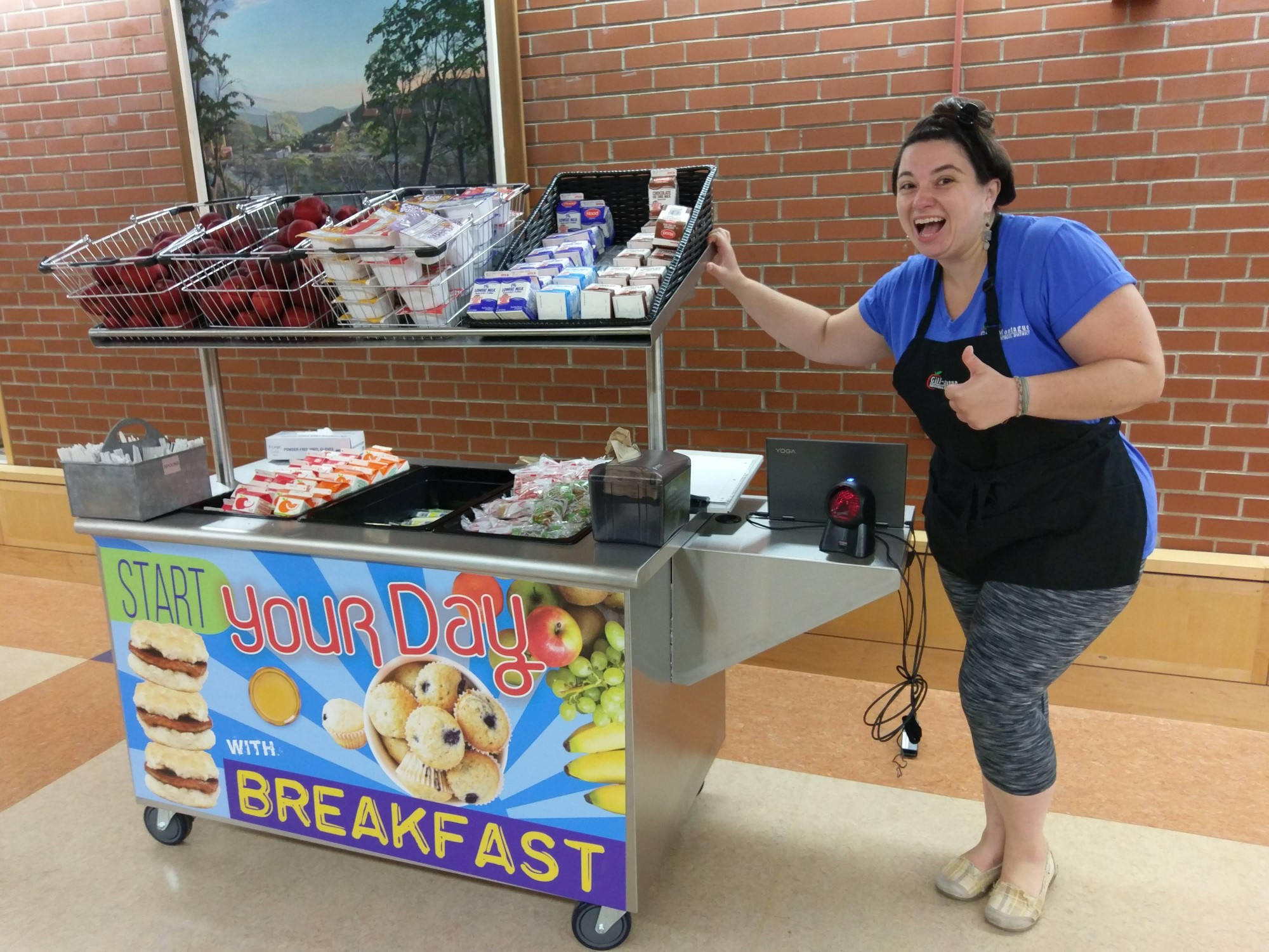 GFMS/TFHS cafeteria manager Liana Pleasant beside the grab-and-go cart, loaded with breakfast items