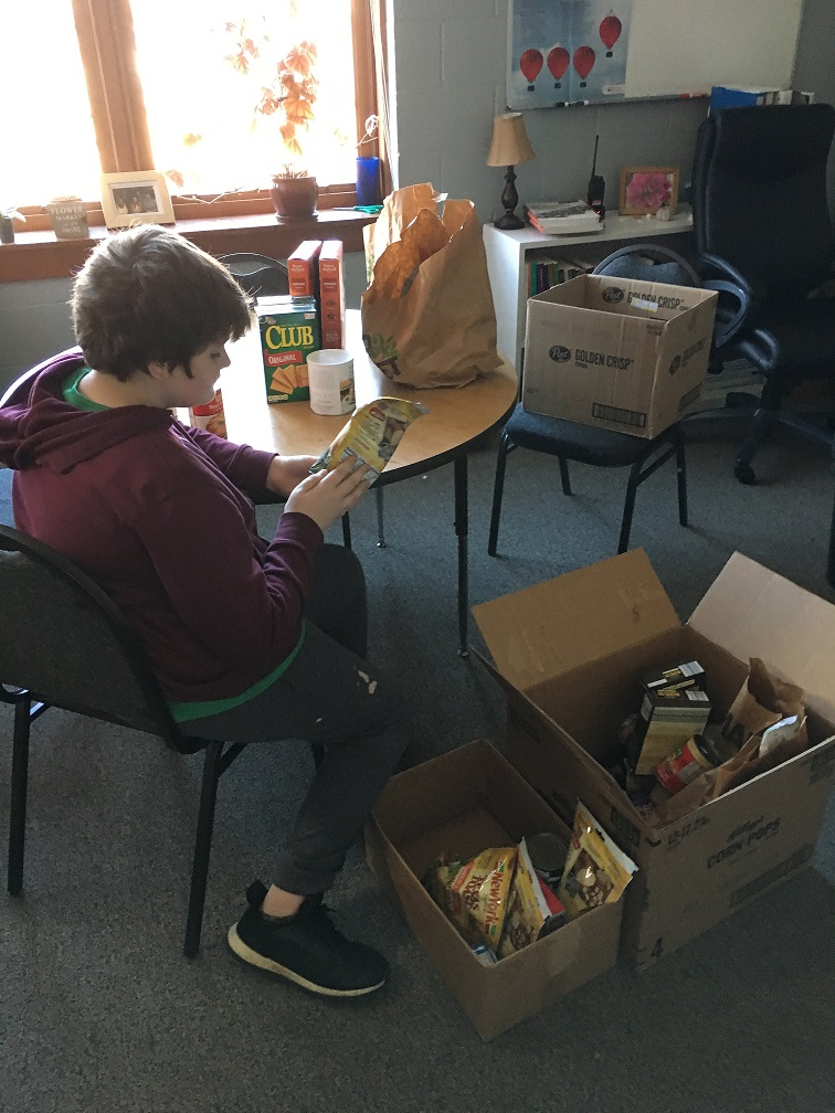 student helper checking expiration dates on food drive donations