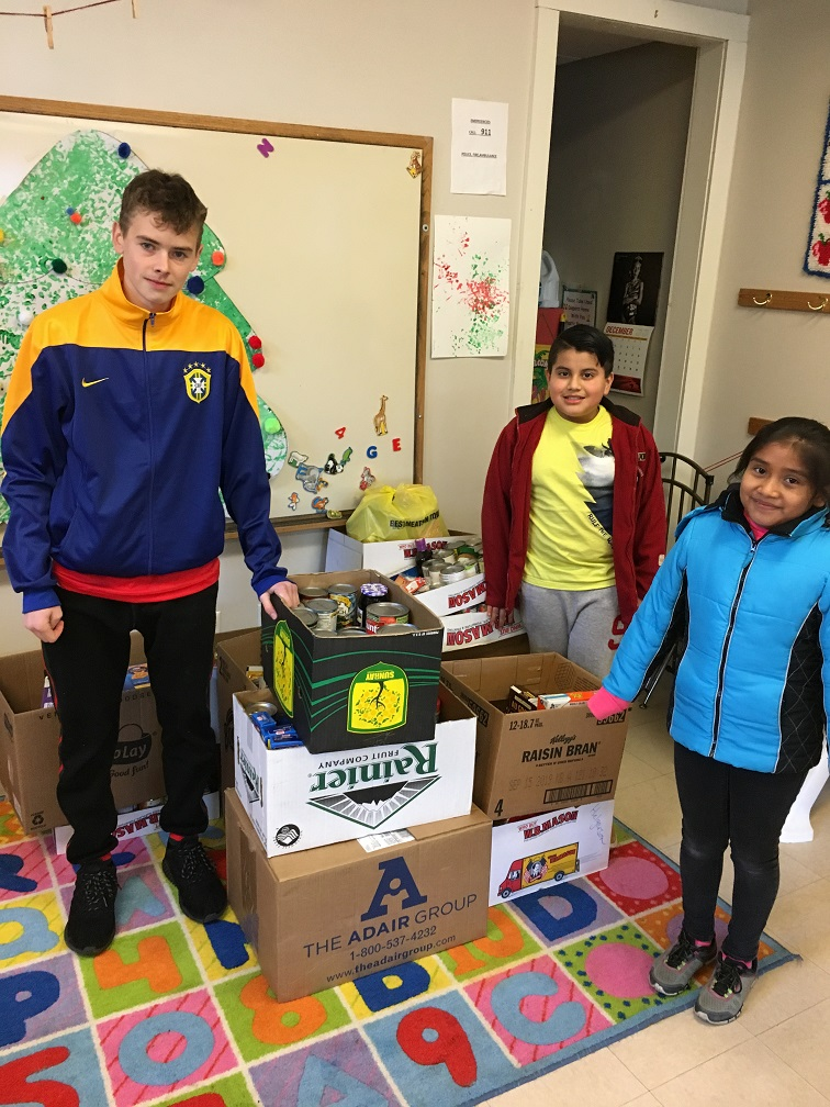 student helpers with boxes of food drive donations delivered on Dec 7