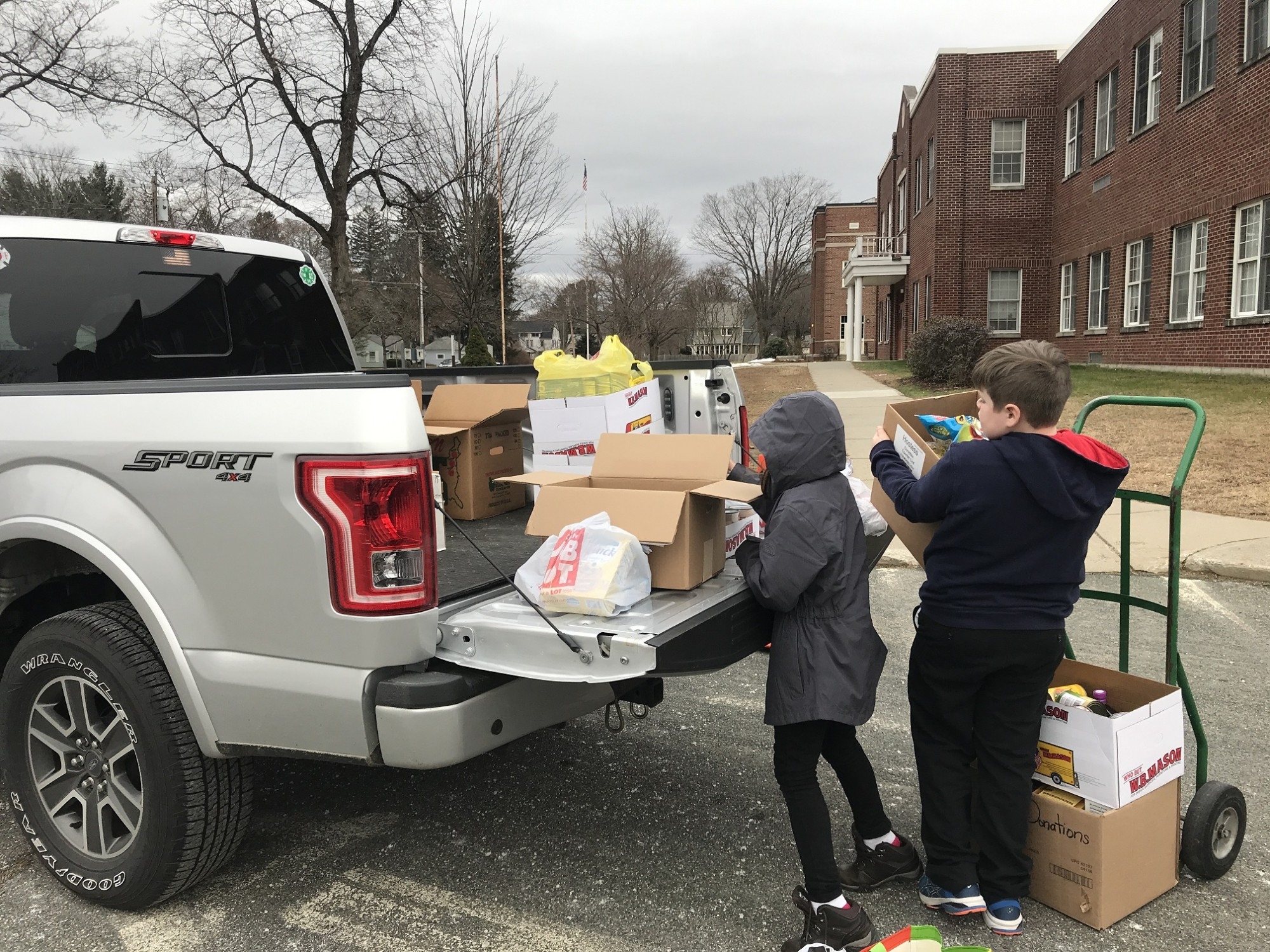 Two 4th grade students help load food drive donations onto a truck.