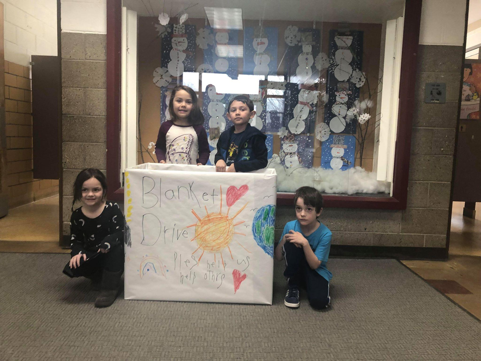 """four kindergarten students posing with a collection box that says """"Blanket drive - Please help us help others"""""""