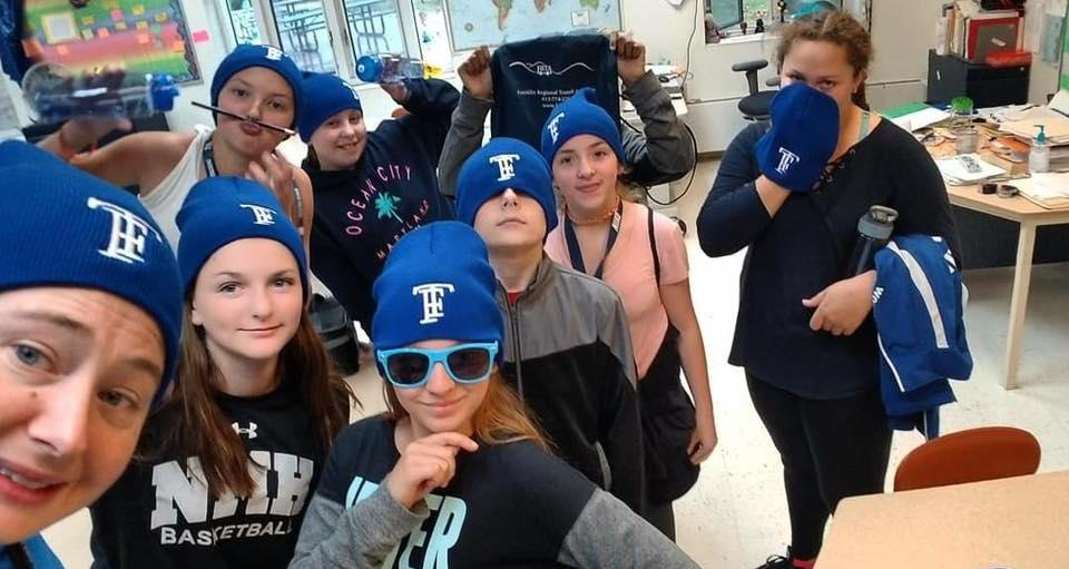 middle school students and tecaher in blue TF hats pose for a selfie