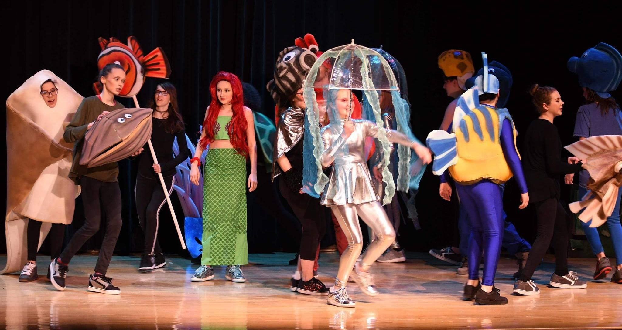 students on stage in fanciful costumes for a production of The Little Mermaid: a flounder, clam, red-haired mermaid (Ariel), jellyfish, clownfish, etc.