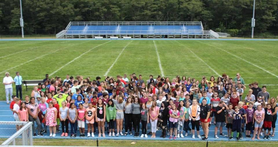 image of large group of students assembled on football field